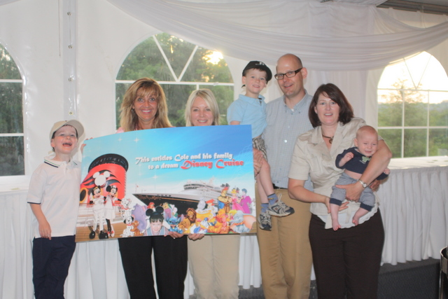 Truck News associate publisher Kathy Penner (second from left) and tournament founder Brenda Grant (third from left) pose with five-year-old Cole (left) and his family after receiving a ticket for a dream Disney cruise at last year's Truck News/Chevron golf tournment.